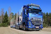 Blue Volvo FH16 750 Timber Truck On Rural Road