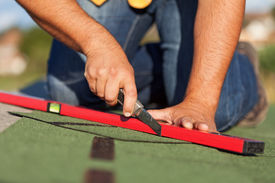 stock photo of shingles  - Worker installing bitumen roof shingles  - JPG