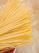 picture of flour sifter  - Raw spaghetti in strainer on wood board with flour - JPG
