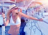 Attractive woman standing on sailboat deck and enjoying mild sunset light, having fun on luxury water transport, summer vacation concept