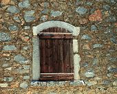 Rough Wooden Shutters In Old Stone Wall