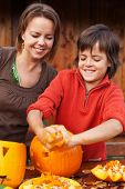 Boy having fun carving a jack-o-lantern for Halloween - removing the seeds