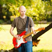 picture of guitarists  - Young guitarist playing guitar in beautiful nature environment - JPG