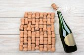HIgh angle shot of a empty champagne bottle with blank label and corks. Closeup on a rustic white wood table. Horizontal format with copy space.