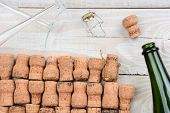 HIgh angle shot of a empty champagne bottle with corks and two flutes. Closeup on a rustic white wood table. Horizontal format.