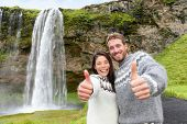 Iceland couple thumbs up wearing Icelandic sweater by Seljalandsfoss waterfall on Ring Road in beautiful nature landscape on Iceland. Woman and man model in typical Icelandic sweater. Multiracial.