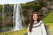 Woman in Icelandic sweater by waterfall on Iceland outdoor smiling. Portrait of beautiful female model in nature landscape with tourist attraction Seljalandsfoss waterfall on Ring Road.