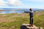 Freedom man in nature on iceland happy with arms enjoying free happiness in beautiful icelandic landscape.  Male hiker relaxing in nature.
