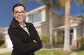 Attractive Mixed Race Woman in Front of Beautiful New Residential House.