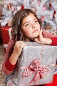 image of sad christmas  - Portrait Of A Sad Little Girl with a present At Christmas - JPG