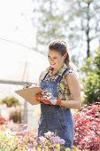 Happy female supervisor writing on clipboard outside greenhouse