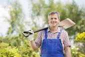 Portrait of happy man carrying spade on shoulder in plant nursery