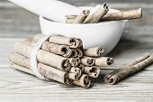 Bunch  of cinnamon sticks and the porcelain mortar with pestle on a wooden background