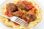 Homemade meatballs in sauce on a bed of fettuccine ribbon pasta  with a fork
