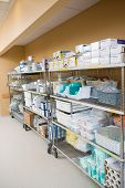 Large group of hospital supplies arranged on trollies in storage room