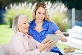 Happy grandmother and granddaughter using digital tablet at nursing home porch