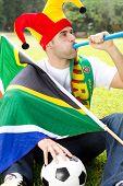 soccer fan blowing vuvuzela on field