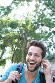 Young Man Laughing With Earphones Outdoors