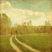 Country road to forest in grunge and retro style.