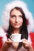 Portrait Woman Wearing Santa Claus Costume With Cup Of Hot Beverage On Blue