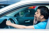 stock photo of deprivation  - Closeup portrait tired young funny man in blue shirt with short attention span driving his black car after long hours trip yawning at wheel isolated outside background - JPG