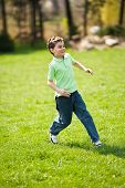 Boy Running On A Meadow