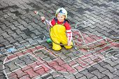 Funny Little Boy Having Fun With Fire Truck Picture Drawing With Chalk.