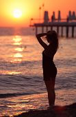 stock photo of say goodbye  - Girl says goodbye to the sea at sunset - JPG