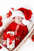 stock photo of christmas baby  - Cute newborn baby wearing Santa Claus hat sleeping in basket - JPG