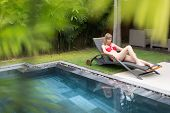 Woman Relaxing On Chaise Longue Near Pool.