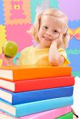 smiling little pre-schoolgirl with an apple and  the books