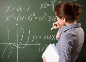 girl writing the mathematical formulas on a chalkboard