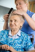 Nurse dressing the hair of a senior woman