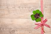Four leaf clover and red ribbon over wooden background