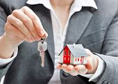 image of house rent  - Real estate agent with house model and keys - JPG