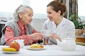 picture of hospice  - Senior woman eats lunch at retirement home - JPG