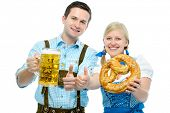 Couple in traditional bavarian tracht holding Oktoberfest beer steins and pretzel