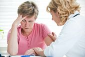 stock photo of terrifying  - Mid adult woman talking to doctor about her diagnosis - JPG