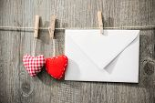 Message and red hearts on the clothesline against wooden background