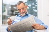 Happy senior man at breakfast with newspaper