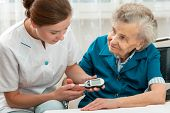 stock photo of measurements  - Female nurse measuring blood glucose level of senior woman - JPG