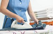 Close up of a woman ironing clothes with a steam iron