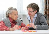 stock photo of geriatric  - Elder care nurse playing jigsaw puzzle with senior woman in nursing home - JPG