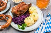 stock photo of pretzels  - Appetizing Bavarian roast pork dish with dumplings and pretzel - JPG