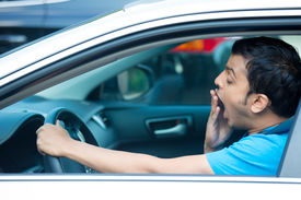 pic of deprivation  - Closeup portrait tired young funny man in blue shirt with short attention span driving his black car after long hours trip yawning at wheel isolated outside background - JPG