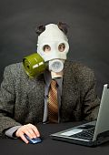 Amusing Person Has Dressed Gas Mask And Works With Computer