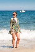 stock photo of girl walking away  - woman walking away on the idylic beach - JPG