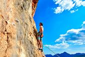 picture of climbing wall  - male rock climber climbs on a rocky wall - JPG