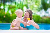 stock photo of sun tan lotion  - Young mother and cute baby boy enjoying summer vacation in a tropical resort at a swimming pool parent applying sun screen using lotion spray for safe tan and skin care - JPG
