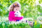 picture of petting  - Adorable little girl cute curly toddler in a colorful summer dress playing with a real rabbit having fun with her pet bunny in a beautiful garden with first spring snowdrop flowers - JPG